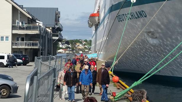 Ei gruppe turistar på veg i land for å ta hamnebyen nærare i augesyn.